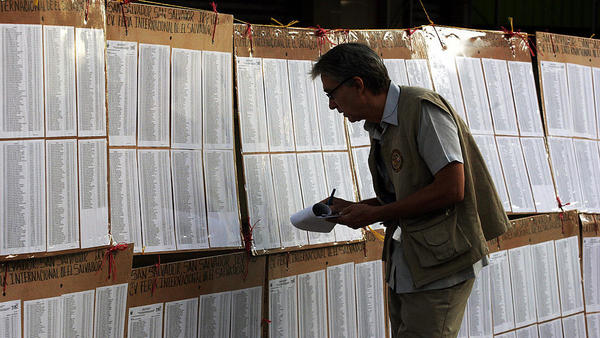 An Organization of American States observer checks the voters register during municipal elections in January 2009 in El Salvador.