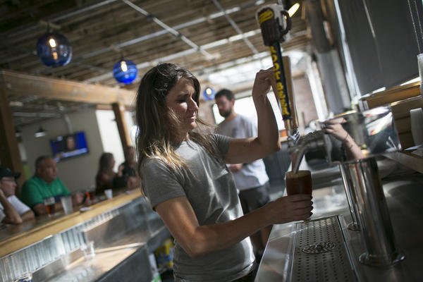 Molly Mattin pours beer at Mother Stewart's Brewing in Springfield. The new brewery, located in an old warehouse space, is part of the city's downtown revival that includes new shops and a farmers market.