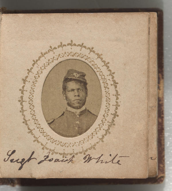 A yellowish brown photograph of Sgt. Isaiah White. He is wearing a buttoned-up jacket with epaulets on the shoulders and a kepi. A bugle insignia is on the front of his kepi. His shoulders are straight and he is directly facing the camera. His kepi is on the left side of his head. His name is inscribed below the photograph on the same page.