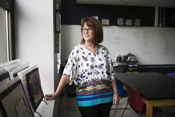 """Debbie Kelly, an art teacher at the Global Impact STEM Academy, stands in her classroom. """"This is a very exciting, happy place,"""" she says of the revived school. """"I think it's just magical."""""""