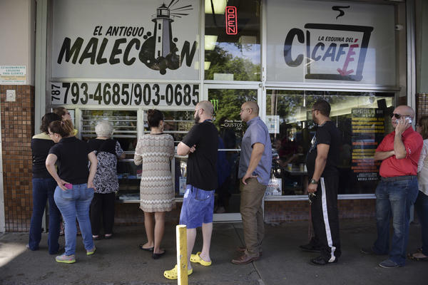 Customers stand in line at one of the few open cafeterias on Roosevelt Avenue, in San Juan, Puerto Rico, on Thursday.