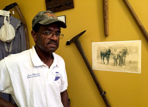 Stanley Madison stands next to a picture of his great-great grandparents at the heritage learning center at Lyles Station.  Madison is the head of the local group working to preserve Lyles Station history. His family has farmed in the area since the 1830s and he continues to farm today.