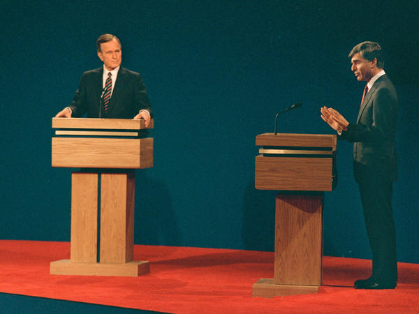 Massachusetts Gov. Michael Dukakis, right, speaks during the second presidential debate alongside his opponent, Vice President George H. W. Bush, in Los Angeles, Calif., on Oct. 13, 1988. A subtle three-inch riser was inserted around Dukakis' podium for height.