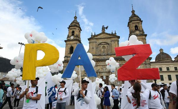 """Colombians in the capital, Bogota, hold up the letters for """"peace"""" in Spanish in September. That agreement between the Colombian government and FARC rebels was rejected by voters in an October referendum. An amended agreement was signed Thursday and is expected to be approved. If implemented, it would end 60 years of nonstop conflict in Latin America."""