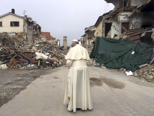 "Pope Francis prays in front of rubble of the quake-struck town of Amatrice, Italy. Francis made a surprise visit Tuesday to the quake zone in central Italy, saying that he wanted ""to be close to the people."""