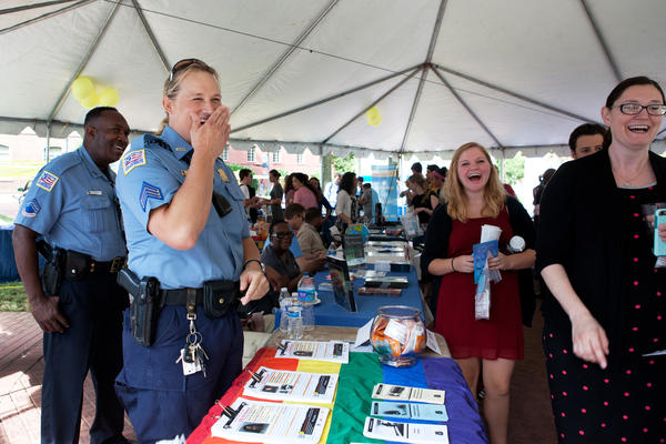 Hawkins laughs with students, teachers and administrators around the LGBT Liaison Unit's booth at the George Washington University Safety & Security Expo.