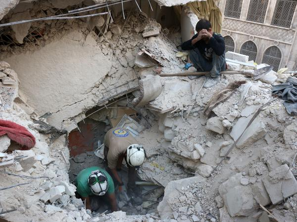 Syrian civil defense volunteers, known as the White Helmets, search for victims amid the rubble of destroyed buildings following a government forces' air strike on the rebel-held neighborhood of Bustan al-Basha in Aleppo on Oct. 4.