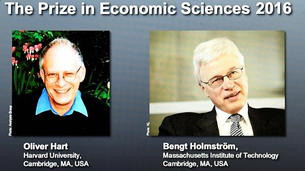 Winners of the Nobel Prize in Economic Sciences, economists Oliver Hart (left) and Bengt Holmström, are displayed on a screen at the Royal Swedish Academy of Sciences in Stockholm on Monday. They won the prize for their work on contract theory.