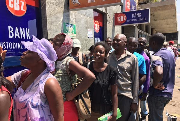 Zimbabweans stand in line for hours outside an ATM at a bank in Harare in order to withdraw U.S. dollars from their accounts. Many fear they will lose access to their dollars when the government introduces new bond notes it says will be equivalent to the U.S. currency.