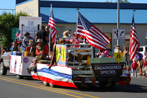 A float with costume-clad ranchers, loggers and miners passes through the center of Burns, Ore., during the annual Harney County Fair parade.