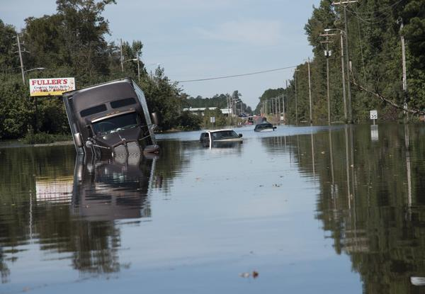 A tractor trailer truck is submerged in floodwaters caused by rain from Hurricane Matthew on Highway NC 211 near the Mayfair neighborhood in Lumberton, N.C., Tuesday, Oct. 11, 2016. Lumberton is about two hours south of Enfield, North Carolina. (Mike Spencer/AP)