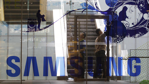 Workers wash a window at a Samsung shop in Seoul, South Korea, on Wednesday as the corporation works out how to clean up its sullied reputation.