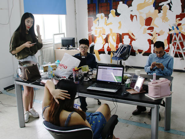 Huang Xian'er (left) looks at her smartphone at the Beijing-based Internet talent company where she works.