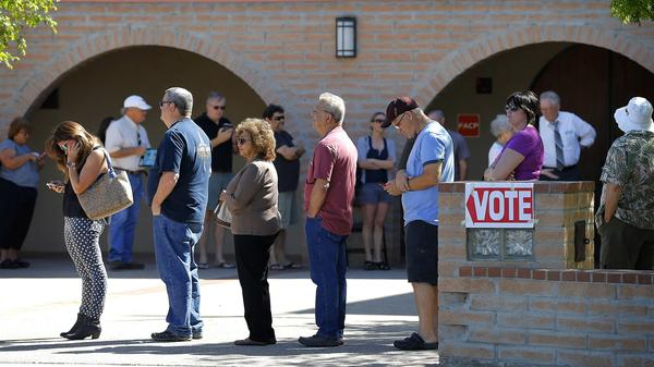 Voters wait in line to cast their ballot in Arizona's presidential primary election in Gilbert, Ariz., in March.