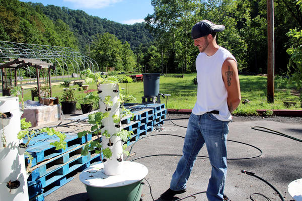 Joel McKinney stands beside a hydroponic tower that is part of his farm outside the Five Loaves and Two Fishes Food Bank.