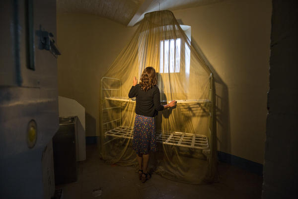 In one cell, British director and artist Steve McQueen has draped a gold-plated mosquito net over a bare metal bunk bed.