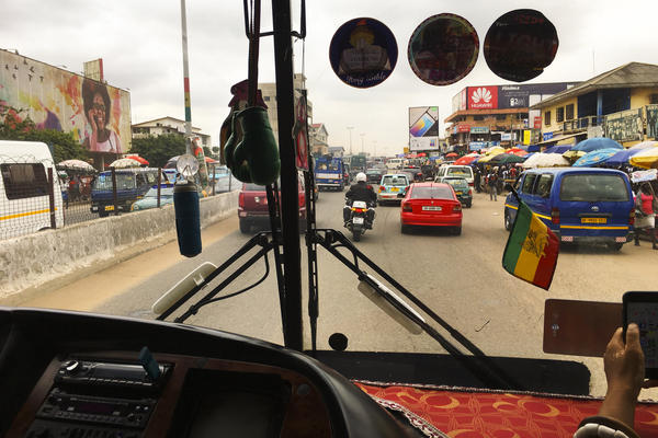"""The <em>tro tros</em> are the ubiquitous vans that serve as group taxis in Accra. Their windshields are adorned with affirmative, often-religious sayings like, """"God Is the Way."""""""