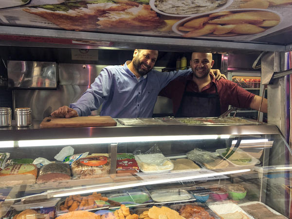 Khaldoun Barghouti (left) and Abdul Rahman Rahim al-Bibi (right), behind the counter at their food truck. The two men say they met behind bars in an Israeli prison, where they worked in the canteen.