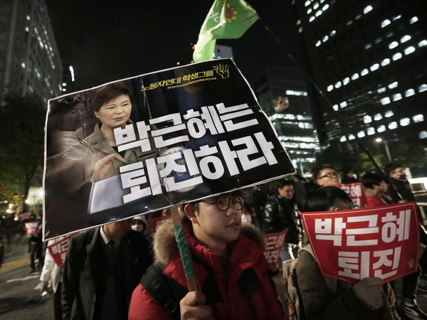 """A South Korean protester carries a placard with images of South Korean President Park Geun-hye and Choi Soon-sil during a rally in downtown Seoul on Wednesday. The placard reads, """"Park Geun-hye should step down."""" South Korean prosecutors requested an arrest warrant for Choi on Wednesday over allegations of influence-peddling and other activities."""