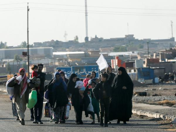 Iraqis living east of Mosul hold a white flag as they flee Wednesday during an Iraqi army's operation to retake the ISIS-held city. So far, the number of civilians fleeing the fighting has been relatively small. But aid groups warn the numbers could rise dramatically as the fighting moves into the city itself.