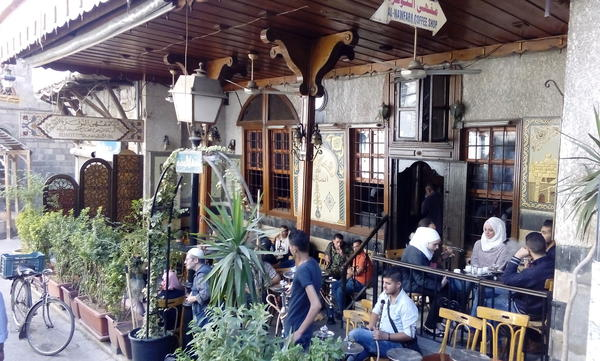 A cafe does a brisk business in Damascus. The city has suffered less damage and the economy still functions compared with many other parts of the ravaged counry.