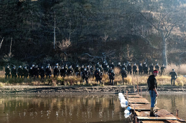 A man stands on a makeshift bridge over the Cannonball River while police officers stand on the opposite shore.
