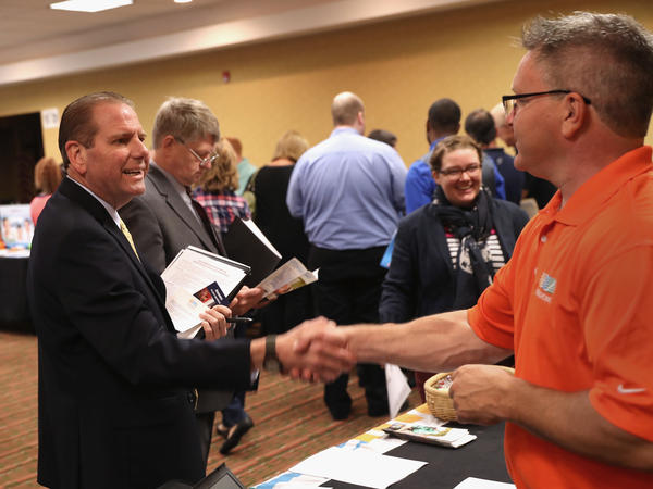 A man speaks with a potential employer Sept. 13 at a job fair in Hartford, Conn. Recent wage gains reflect the steady healing of the labor market since the worst of the Great Recession.