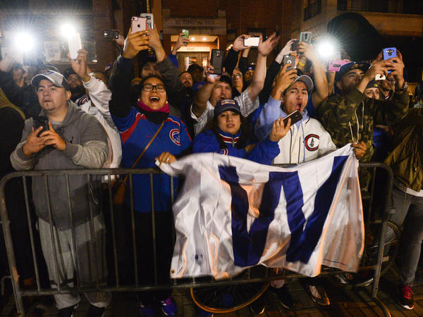Fans celebrate outside Wrigley Field as buses carrying the Chicago Cubs baseball team arrive in Chicago early Thursday, Nov. 3, 2016, after the Cubs defeated the Cleveland Indians 8-7 in Game 7 of the World Series in Cleveland.