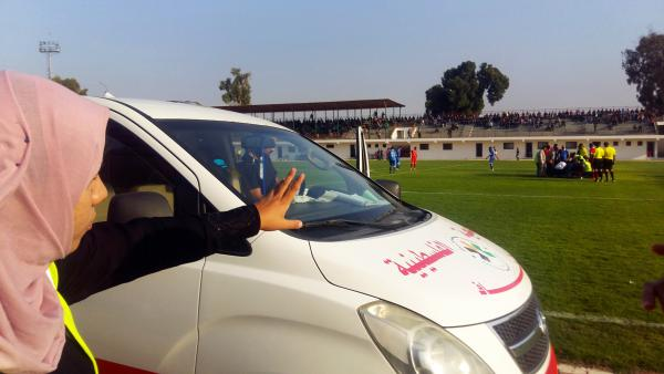 Hanan Abu Qassem motions from the sidelines of a top division professional soccer game in Gaza, poised to treat injured players. Abu Qassem is the first female EMT to staff such games in the Gaza Strip.