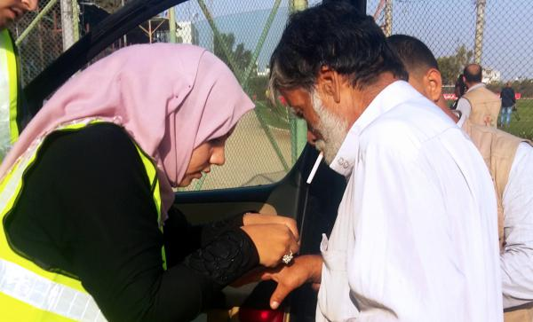 Hanan Abu Qassem (left) treats Kamal Bahoum (right), a soccer fan injured during scuffles at the gate to Gaza's main soccer stadium. The presence of female EMTs at the soccer games has stirred controversy, and Abu Qassem has been warned she may be barred from future games.