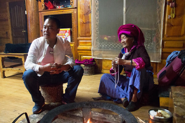 "Zhaba Songding and his maternal grandmother Ani Ciru warm themselves by the hearth in their traditional living room, known in Mosuo culture as a ""grandmother's room."""