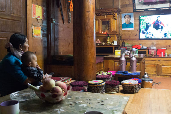 Zhaba Songding's mother Cili Zhuoma and his son, Luosang Nima, watch television at home.
