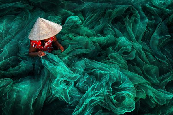 In a village in southern Vietnam, a woman weaves a fishing net. By tradition, Vietnamese women make nets for their husbands.
