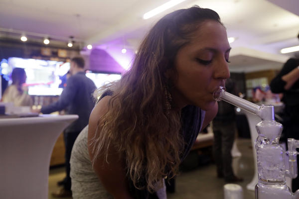 Krystal Xiques smokes marijuana at a rally in support of Prop 64 at Sparc Dispensary in San Francisco on Tuesday.