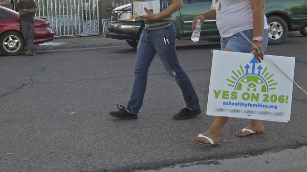 Workers with the Living United for Change in Arizona organization canvas a south Phoenix neighborhood in October to advocate for the passage of Proposition 206, which would increase the state's minimum wage. The measure was approved on Tuesday.