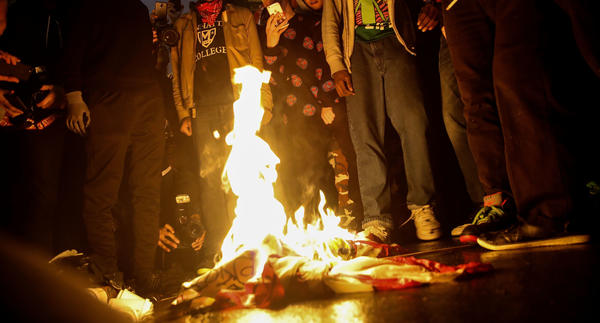 Protestors burn an American flag outside of Trump Tower in New York City on Wednesday.