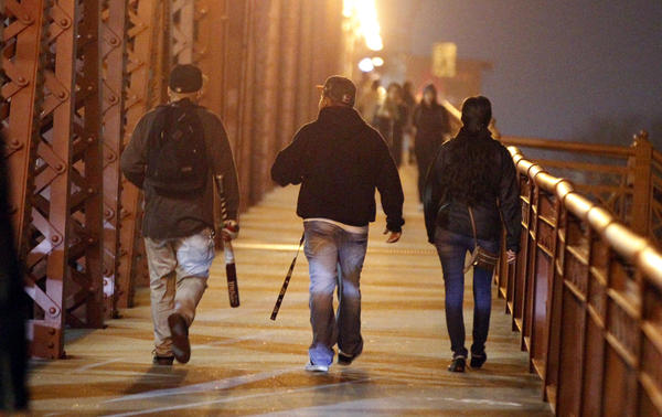 A demonstrator with a baseball bat crosses a bridge during a protest against the election of Donald Trump in Portland, Ore., on Thursday night.