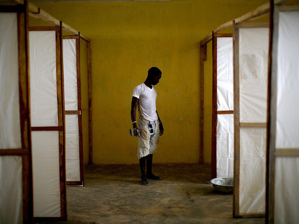 A worker stands near dividers intended to separate patients in an Ebola treatment facility under construction in the Port Loko district of Sierra Leone in 2014.