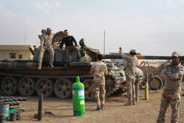 Iraqi soldiers pose on a tank they captured from ISIS in a small base a few miles east of Mosul.