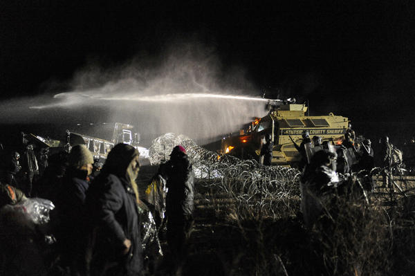 Police use a water canon to spray protesters during a clash overnight near Cannon Ball., N.D.