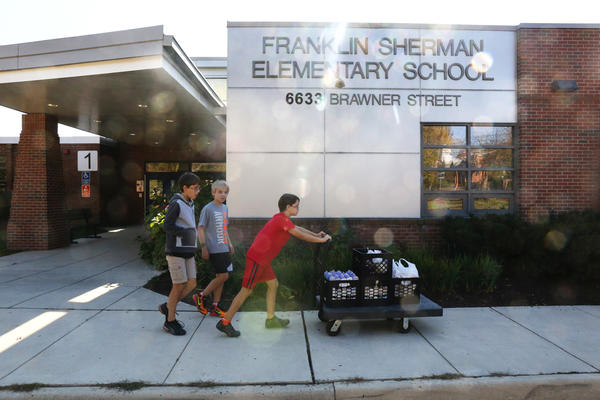 Franklin Sherman Elementary students Nicola Hopper, 11, Jake Hensley, 11, and Aya Hopper, 10, transport collected food from their school to McLean Baptist Church, located across the street from the school.