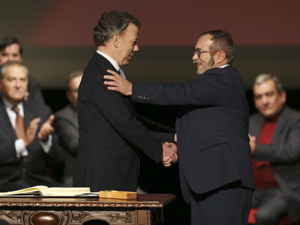 Colombia's President Juan Manuel Santos (left) shakes hands with with FARC leader Rodrigo Londono, known as Timochenko, after signing a revised peace pact in Bogota, Colombia, on Thursday.