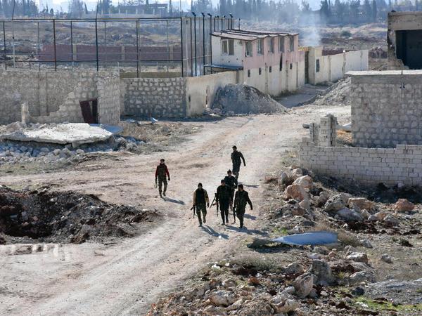 Syrian pro-government forces walk past damaged houses in eastern Aleppo, near Masaken Hanano, on November 23.