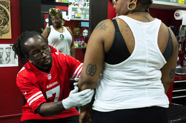 Christopher Mensah, owner and tattoo artist at the Pinz-N-Needlez tattoo shop in Washington, D.C., creates the outline for Oshun Afrique's 35th tattoo.