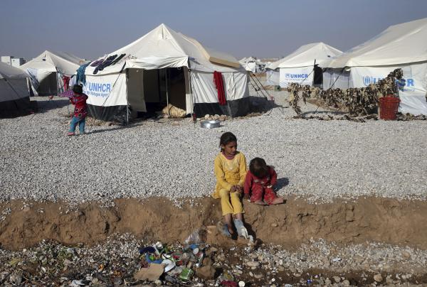 Displaced Iraqi children who fled Mosul with their parents sit outside their tent at a camp for internally displaced people in Hassan Sham, east of Mosul, on Nov. 12. Many children stopped attending school because of the ISIS takeover and their parents are eager to see them back in the classroom.
