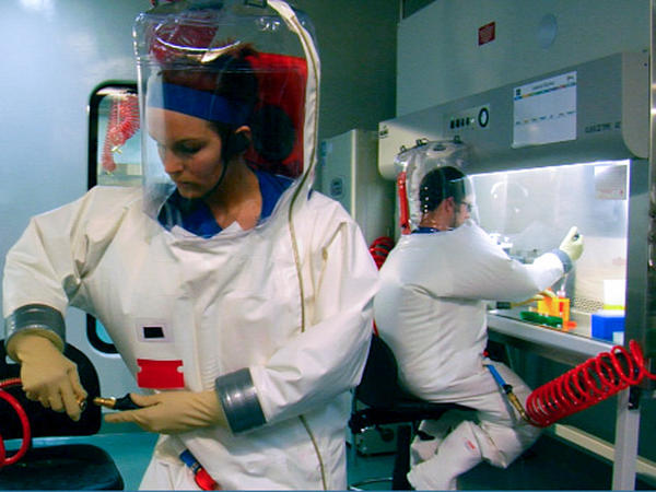 Two scientists are suited up for work inside the Biosafety Level 4 lab in Montana.