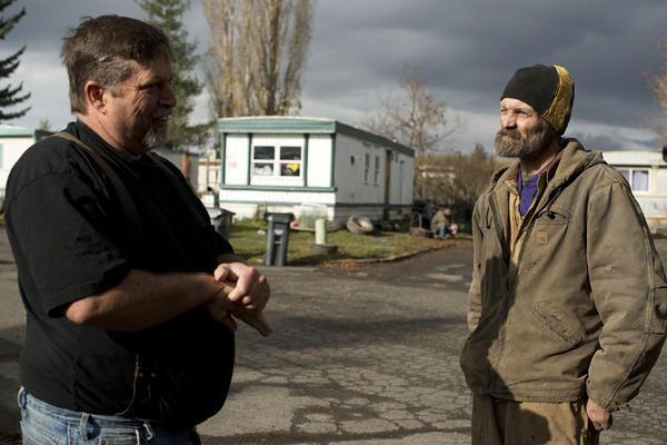 James Ware (left) speaks with fellow Syringa resident Reggie Thistlewait. Ware had been warning government officials for years that there were chronic problems in Syringa, but little had changed.