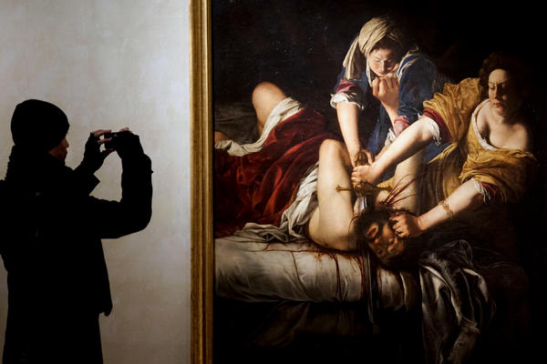 """A visitor takes a photo of <em>Judith Slaying Holofernes</em> by Italian 17th century artist Artemisia Gentileschi, on display at Rome's Palazzo Braschi museum. The """"Artemisia Gentileschi and Her Times"""" exhibition will run till May 7, 2017."""