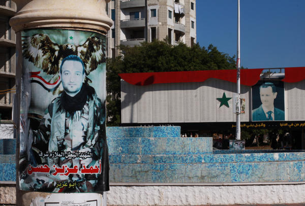 A poster memorializing a man who died fighting on the government's side is displayed in Tartus near a picture of Syrian President Bashar Assad at a memorial including a list of thousands of names of men killed in the war. The coastal city has a heavy population of Alawite Muslims, belonging to the same sect as Assad.