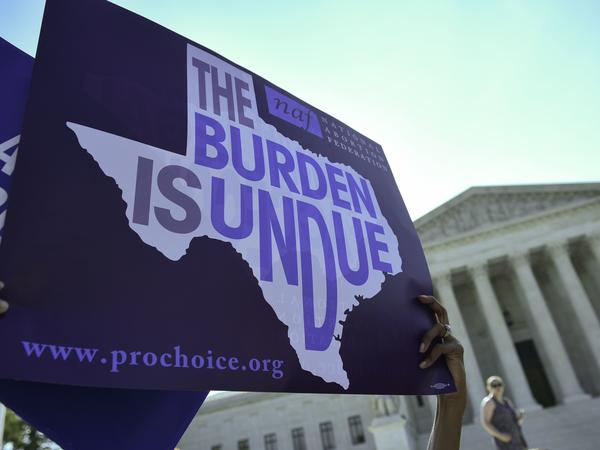 An abortion rights activist holds a sign outside the U.S. Supreme Court earlier this year before the court struck down a Texas law placing restrictions on abortions. Now abortion rights supporters are suing the state again over a new rule.